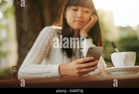 Young chinese woman looking at mobile phone in her hand while sitting at outdoor cafe. Asian female model reading - Stock Photo