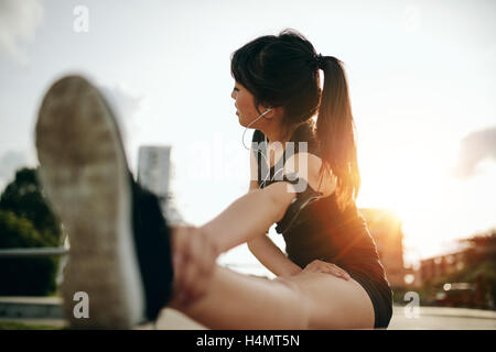 Shot of young woman stretching her legs after a run in the city. Female runner exercising in morning. - Stock Photo