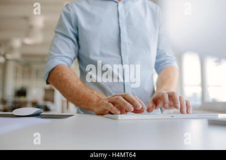Close up of businessman hands typing on computer keyboard. Cropped shot young man working on computer while standing - Stock Photo