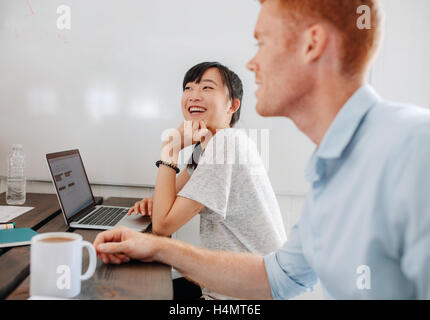 Two happy young business people sitting at conference table during business meeting. Coworkers sitting in boardroom - Stock Photo