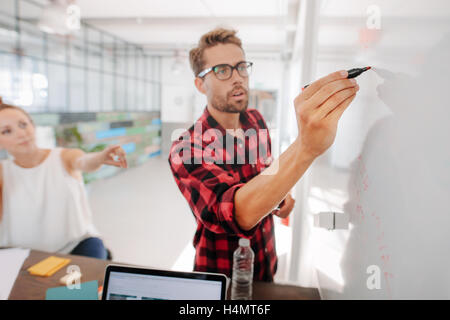 Casual young executive giving a presentation on white board to coworkers. Businesspeople discussing business ideas - Stock Photo