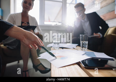 Shot of business people in a meeting at office, with woman pointing at charts. Corporate professional discussing financial growt