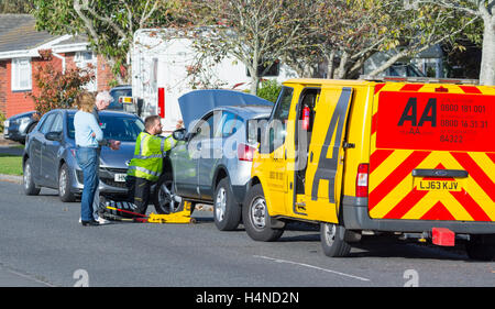 AA recovery van and mechanic at a broken down car in the UK. AA rescue service. - Stock Photo