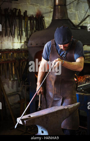 A blacksmith in a leather apron holds a thin length of metal against anvil in a workshop. - Stock Photo