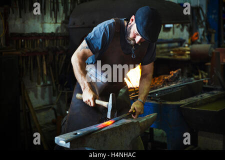 A blacksmith strikes a length of red hot metal on anvil with a hammer in a workshop. - Stock Photo
