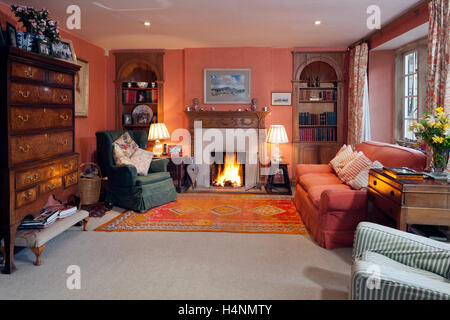 A cosy traditionally furnished living room with antique furniture and a roaring open fire - Stock Photo