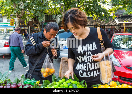 Sale, shopping and people concept - Chinese young woman choosing ripe organic fruits at street - Stock Photo
