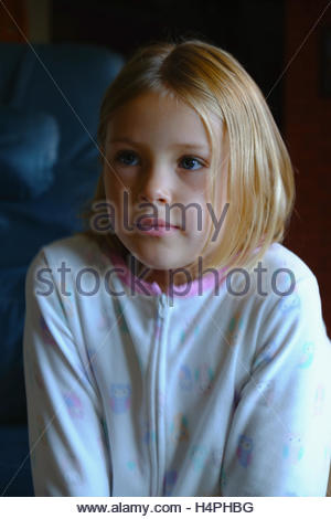 A six year old girl, wearing pajamas, watches cartoons on the television. - Stock Photo