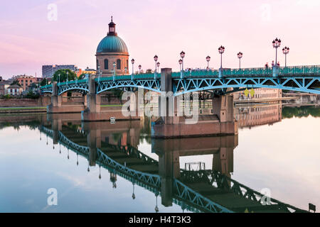 Saint-Pierre Bridge reflecting in Garonne river and Dome de la Grave at sunset in Toulouse, France - Stock Photo