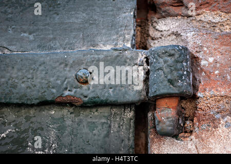 Detail of antique metal gate with hinge and old brick wall. Toulouse, France. - Stock Photo