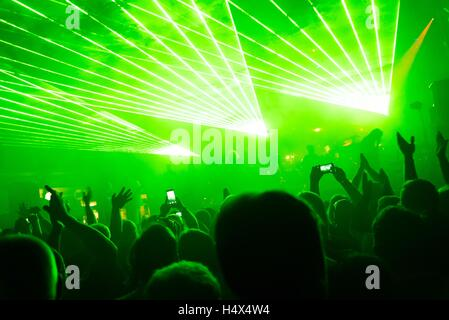 Rock concert, silhouettes of happy people raising up hands in front of bright, green stage laser lights. Space in - Stock Photo