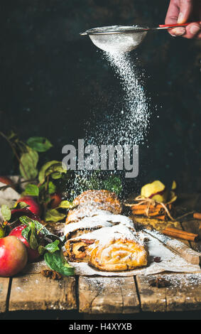 Man's hand with sieve sprinkling sugar powder on apple strudel - Stock Photo