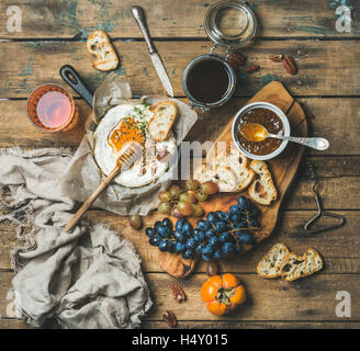 Cheese, fruit and wine set over rustic wooden background - Stock Photo