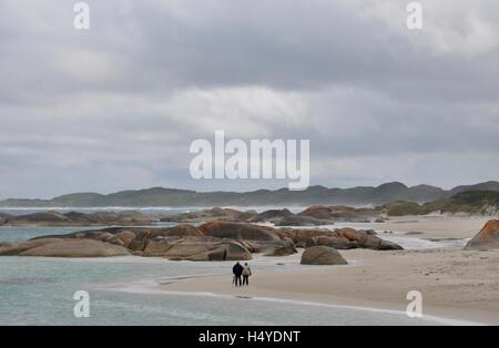 Denmark,WA,Australia-October 2,2014:Elderly couple walking the Green's Pool remote and rocky beach during a storm - Stock Photo