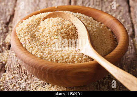 The dry couscous in a wooden bowl with a spoon close-up on the table. horizontal - Stock Photo