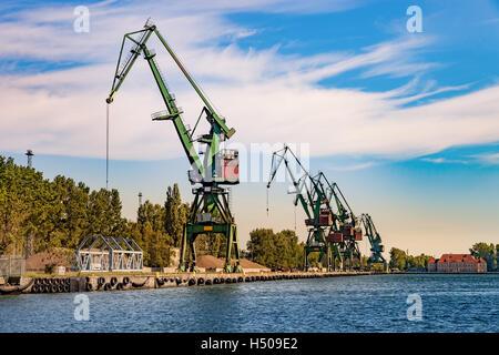 Port cranes for unloading sand on ship. - Stock Photo