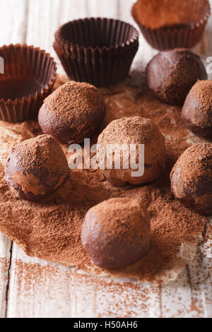 Chocolate truffles with cocoa powder macro on a wooden table. Vertical - Stock Photo