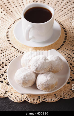 Coffee and polvoron cookies with powdered sugar close-up on a plate. vertical - Stock Photo