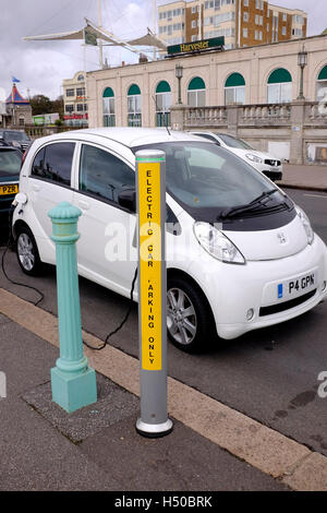 Peugeot car at an electric car charging point on Brighton seafront UK - Stock Photo