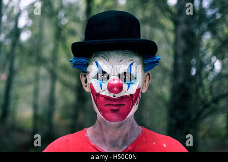 closeup of a scary evil clown wearing a bowler hat in the woods - Stock Photo