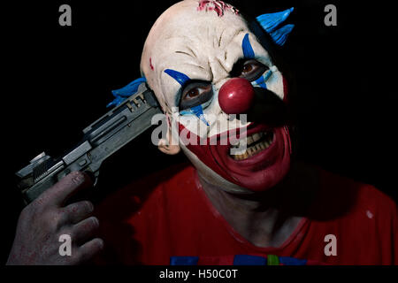closeup of a scary evil clown pointing a gun to his own temple in the darkness - Stock Photo
