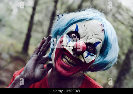 closeup of a scary evil clown in the woods touching his blue hair and smiling - Stock Photo