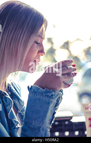 Portrait of young woman drinking coffee - Stock Photo