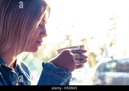 Portrait of young woman drinking caffee - Stock Photo