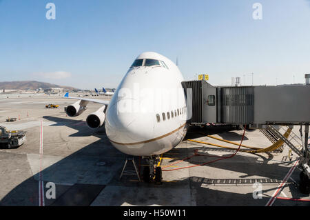 Focus on the nose of a passenger aircraft that is parked at airport gate and connected to a jet bridge. - Stock Photo
