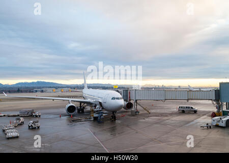 A commercial aircraft on the tarmac being serviced at the passenger terminal of Vancouver International Airport - Stock Photo