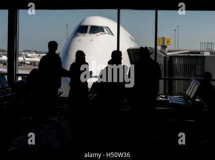 Silhouette of passengers waiting at the airport gate with the nose of an aircraft outside on the airport tarmac. - Stock Photo