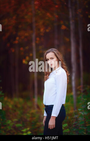 Beautiful woman in the autumn forest. Young brunette girl - Stock Photo