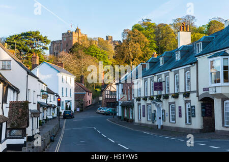 The picturesque village of Dunster in Somerset with the castle perched on the hill above the village framed by the - Stock Photo