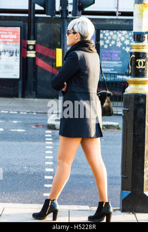 A woman waiting for a taxi cab in Kensington, London, UK - Stock Photo