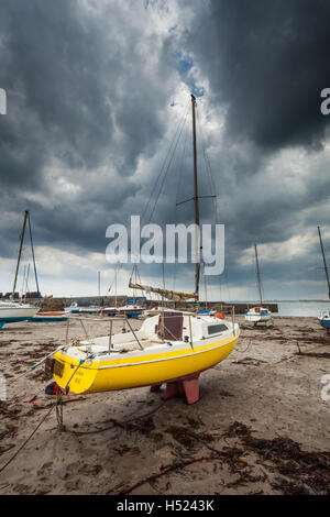 A yellow moored sail boat called 'The Curlew' on a sandy beach in Northumberland on the North East coast of England - Stock Photo