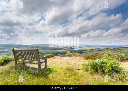 Wooden bench overlooking a wonderful view over the valley to the distant hills on a bright and cheery sunny day, - Stock Photo