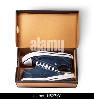 Dark blue sports shoes inside cardboard box isolated on white background - Stock Photo