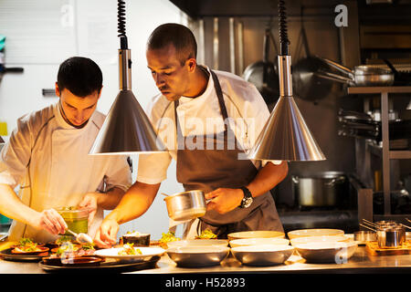 Two chefs in a restaurant kitchen, plating food. - Stock Photo