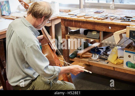 A violin maker in his workshop playing instrument with a bow, tuning and finishing. - Stock Photo
