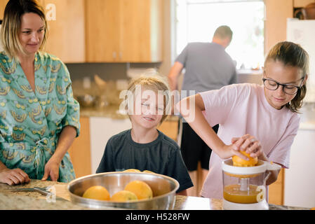 Family preparing breakfast in a kitchen, girl squeezing oranges. - Stock Photo