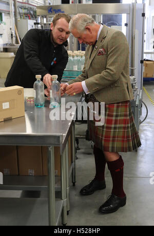 The Prince of Wales, known as the Lord of the Isles while in the Western Isles, puts a the label on a bottle of - Stock Photo
