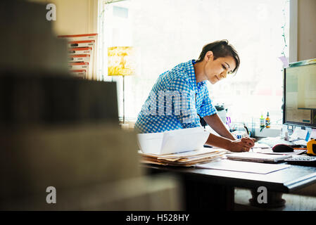Woman working at a desk in interior design studio and accessories store. - Stock Photo