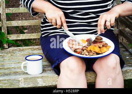 Woman sitting on a bench, eating from a plate of food balanced on her knees. - Stock Photo