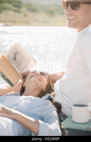Man and woman reclining on a jetty, reading a book. - Stock Photo