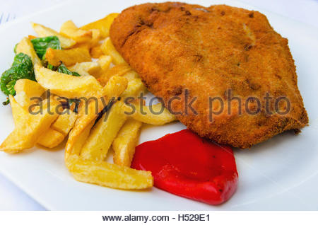 Asturian cachopo with fried potatoes and green peppers, and a red pepper. - Stock Photo