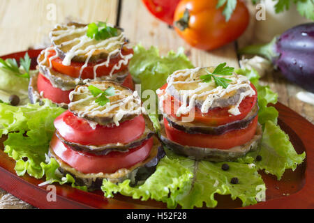 Fried eggplant a stack of folded with tomato, garlic and cream sauce on salad leaves. - Stock Photo