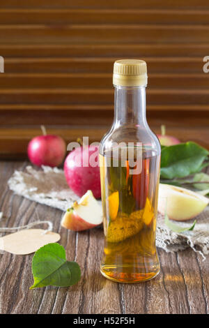 Apple cider vinegar in a glass bottle with fresh apples on a wooden table. Copy space for your text. - Stock Photo