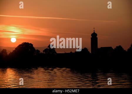 River Danube sunrise with German church. - Stock Photo
