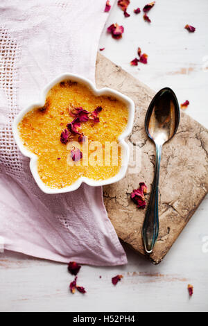 Homemade creme brulee with edble pink roses - Stock Photo