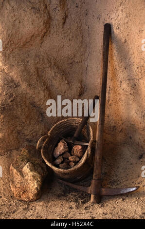 Ancient mining tools and basket full of rocks inside a tunnel in a mine - Stock Photo